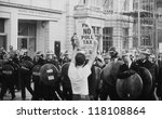 Small photo of LONDON - MARCH 31: A protestor holds up a poster in front of riot police during the Poll Tax Riots on March 31, 1990 in London. The demonstration was against the unpopular Community Charge.