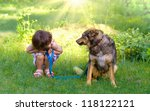 Stock photo happy little girl playing with big dog in the garden 118122121