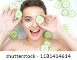Small photo of Portrait of beauty caucasian female woman with clean pure skin taking spa relaxing in bath with cucumber slices white soap shampoo water. Skin beauty health care concept. Body part bare shoulder