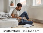 Small photo of Relaxed concentrated bearded man enjoys reading detective story, focused in book, sits on floor in bedroom, holds mug with coffee or tea, has beard, enriches his knowledge in financial sphere