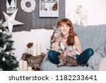 Stock photo young pretty smiling woman sitting on the chair with four cats pets comfort rest and people 1182233641