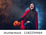 Small photo of beautiful woman in vampire costume smiling on dark background with smoke