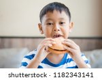 happy asian boy eating... | Shutterstock . vector #1182343141