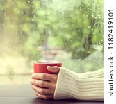 red mug of hot drink in hand on ... | Shutterstock . vector #1182419101