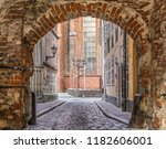 a red brick arch leading to a... | Shutterstock . vector #1182606001