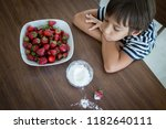 kid eating strawberry with sugar | Shutterstock . vector #1182640111