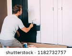 man painting a wardrobe with a... | Shutterstock . vector #1182732757