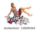Woman and her shoes - Happy female shopaholic posing on white background behind a large selection of high heel shoes - stock photo