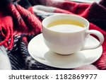 cup of tea on red warm woolen... | Shutterstock . vector #1182869977