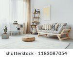 pouf in front of wooden couch... | Shutterstock . vector #1183087054