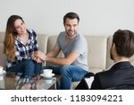 Small photo of Happy couple sit on couch holding hands, look at psychologist thanking for saving marriage, loving husband and wife reconciled at therapy session, relationship expert help spouses to make peace