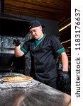 the cook prepares pizza in... | Shutterstock . vector #1183176637
