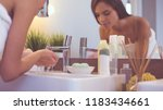 young woman washing her face... | Shutterstock . vector #1183434661
