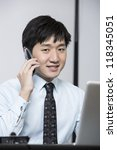 Chinese business man on phone while sitting at his desk - stock photo