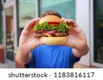 teen boy holding a hamburger in ...   Shutterstock . vector #1183816117