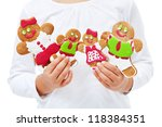 Child hands with happy gingerbread people family - holidays are coming - stock photo