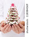 Woman and child hands holding gingerbread decorated christmas tree - shallow depth - stock photo
