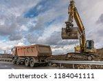 excavator unloading dirt and... | Shutterstock . vector #1184041111