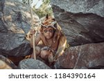Small photo of Caveman, manly boy hunting outdoors. Prehistoric tribal boy outdoors on nature. Young shaggy and dirty savage, warrior and hunter hiding in an ambush behind a stone. Primitive ice age man in animal