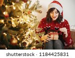 happy young woman in santa hat... | Shutterstock . vector #1184425831