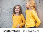two little girls stand and... | Shutterstock . vector #1184624671