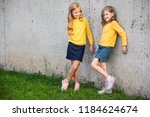 two little girls stand and... | Shutterstock . vector #1184624674