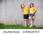 two little girls stand and... | Shutterstock . vector #1184624707