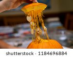 Small photo of The hand of a man pulls the top of a Halloween pumpkin ready to scoop out the inside guts and seeds so it can be carved into a Jack-O-Lantern. Several seeds are caught in stringy guts of the pumpkin.