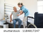 Small photo of Smiling nurse assisting senior man to get up from bed. Caring nurse supporting patient while getting up from bed and move towards wheelchair at home. Helping elderly disabled man standing up.