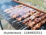 frying pork on a skewer over a...   Shutterstock . vector #1184832511