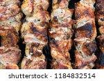 frying pork on a skewer over a...   Shutterstock . vector #1184832514