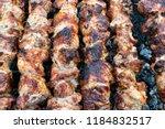 frying pork on a skewer over a...   Shutterstock . vector #1184832517