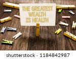 Small photo of Text sign showing The Greatest Wealth Is Health. Conceptual photo being in good health is the prize Take care Clothespin holding white paper note several clothespins wooden floor.