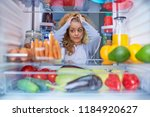confused hungry woman holding...   Shutterstock . vector #1184920627