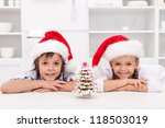 Happy christmas kids in the kitchen with their gingerbread decorated tree - stock photo