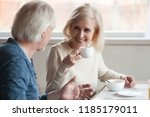 Smiling beautiful middle aged mature woman drinking coffee tea listening to older man talking during breakfast, senior happy family couple eating having pleasant conversation on date at home in café