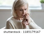 upset middle aged woman wiping... | Shutterstock . vector #1185179167
