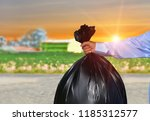 hand is holding a garbage bag... | Shutterstock . vector #1185312577