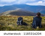 girl sitting in the mountains.... | Shutterstock . vector #1185316204