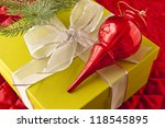 Christmas decoration and gift box on red quilted christmas tree skirt. - stock photo