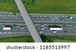 Small photo of AERIAL, TOP DOWN: Colorful vehicles move along the busy freeway and under a concrete overpass. Flying above cars and trucks driving up and down a bustling highway running through the green nature.
