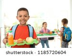 Stock photo african american boy holding tray with healthy food at school canteen 1185720604