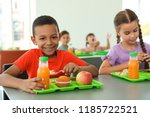 Stock photo children sitting at table and eating healthy food during break at school 1185722521
