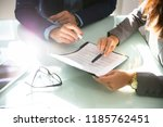 two businesspeople hand... | Shutterstock . vector #1185762451