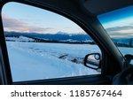 Evening twilight winter Chornohora mountain ridge scenery view through car windshield (Ukraine, Carpathian Mountains, Hoverla, Petros and other alps from Yablunytsia pass). Car model unrecognizable.