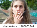 young pretty girl smoking a... | Shutterstock . vector #1186009264