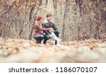 Stock photo woman and man petting the dog walking her in a colorful fall setting having fun in nature 1186070107