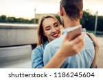 couple hugs and using gadgets ... | Shutterstock . vector #1186245604