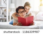 grandmother reading a book to... | Shutterstock . vector #1186339987