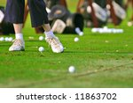 senior golfer practices at the driving range - stock photo